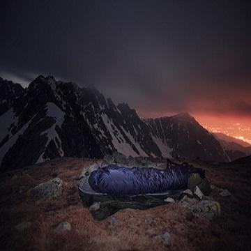 Der Schlafsack. Tourist in Schlafsacklager im Hochgebirge. Nachtfotografie im Freien mit schöner Landschaft.