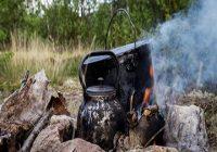 Kochen unterwegs. Topf und Wasserkanne im Lagerfeuer.