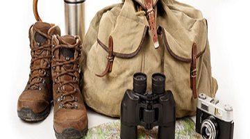 Wanderausrüstung. Rucksack Wanderschuhe Fernglas Kamera Landkarte Thermoskanne und Wanderstock.