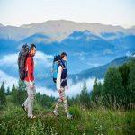 Wanderwege In den Bergen wandern. Der Kerl und das Mädchen mit Rucksäcken sind auf dem Weg auf einem Hügel mit einer schönen Landschaft von Bergen im Dunst. Konzept des aktiven wandernden Lebensstils im Freien.