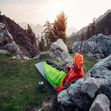 Zelten am Berg. Männlicher Wanderer, trinkt Kaffee und genießt nebelhafte Landschaft.