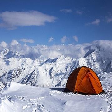 Zelten im Winter. Orangenes Zelt im Schnee in den Bergen.