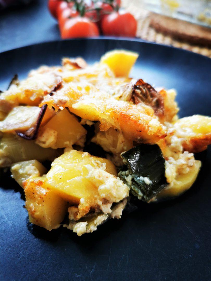 Schneller vegetarischer Kartoffelauflauf mit Lauch und Zwiebeln auf einem schwarzen Teller. Ein traumhaft einfaches Kochrezept