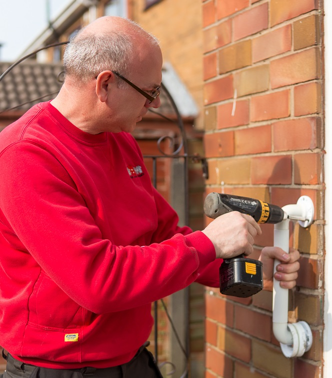 A Care and Repair worker fixing a grab rail to a wall