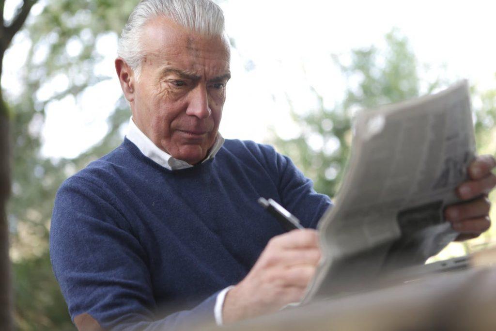 Rentner entspannt beim Zeitung lesen