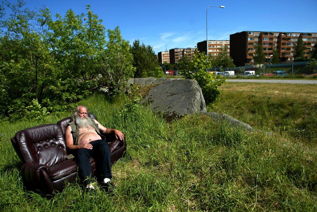 Soffan i brunt skinn är ett av Örjans alla fynd från containrar i Fisksätra. Örjan har ställt den i gröngräset, ett stenkast från sin husvagn på lastbilsparkeringen.