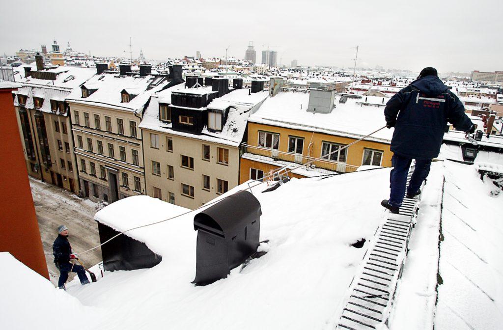 Roger Ronny Tommy *** Local Caption *** Plåtslgare som röjer snö från taket