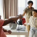 Eltern mit Mädchen und Schulrucksack
