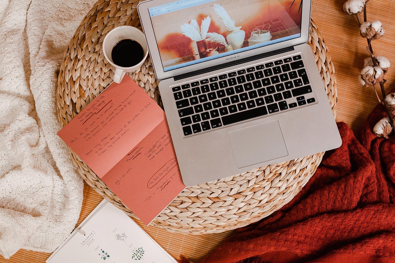 Computer på bord med kaffe og notesbog