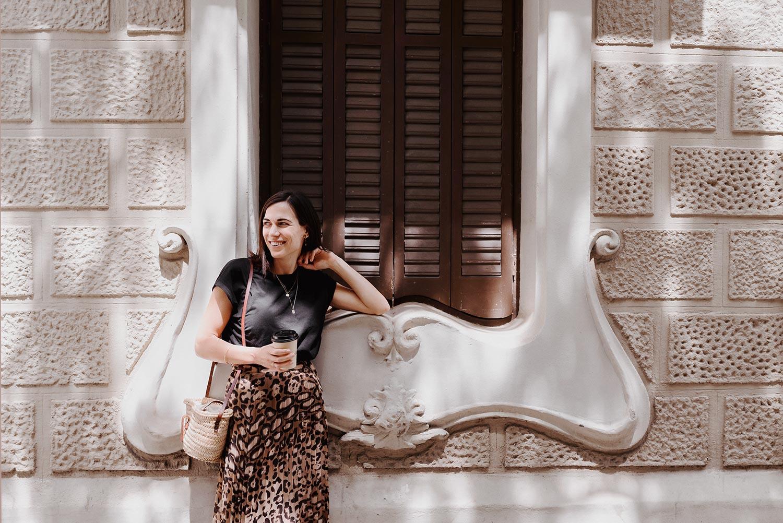 Christina med kaffe i hånden foran smuk bygning