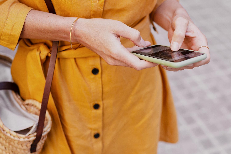 Christina holder en mobil i hånden
