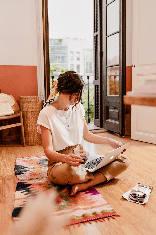 Christina sidder på gulvet med computeren