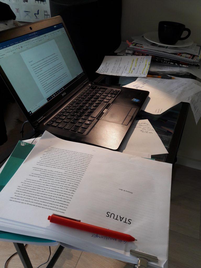 skirivebord med romanen STATUS