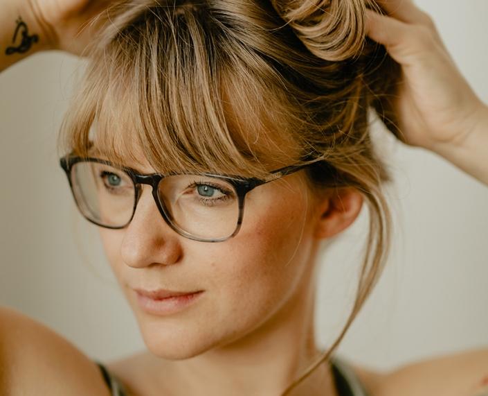 Eine Frau mit Brille greift mit beiden Händen in ihre Haare