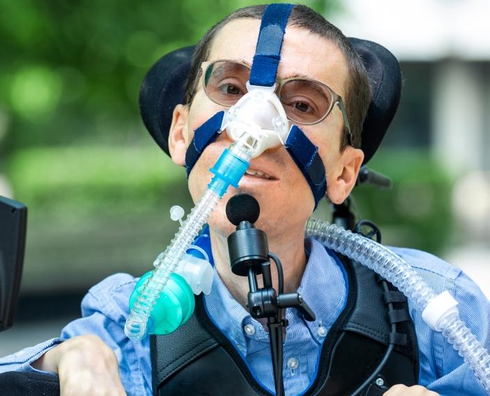 Marcel Renz sitzt im Rollstuhl mit Beatmungsmaske und lacht in die Kamera