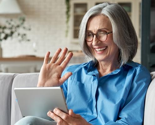 Eine ältere Dame winkt lachend in ein Tablet