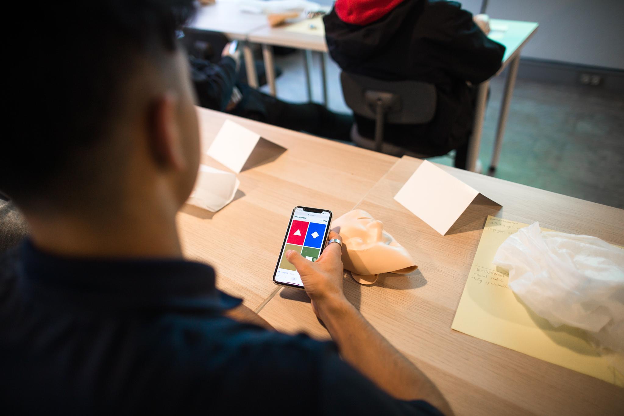 sidder-med-mobil-til-foerstehjaelpskursus