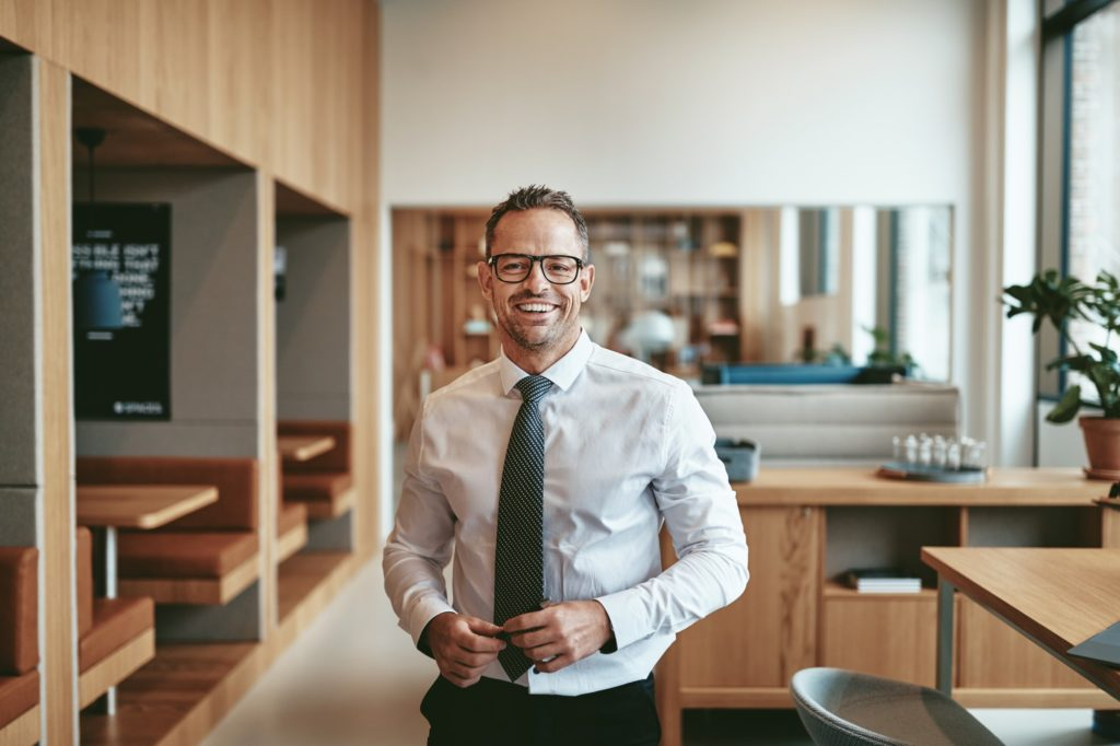 Smiling mature businessman standing alone in an office cafeteria