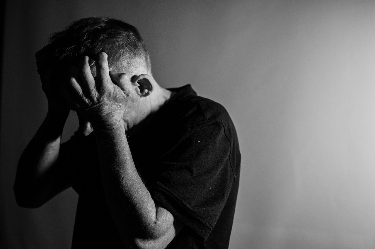 Black and white photo of man feeling grief after loss of family