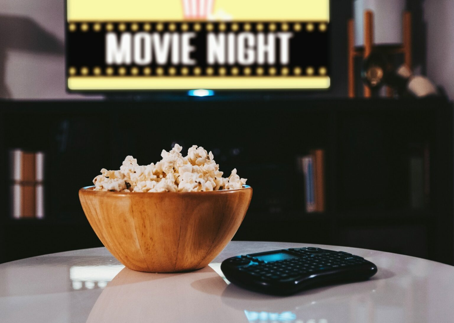 Bowl of popcorn, tv in background, movie night, home, lifestyle, remote, watching tv.