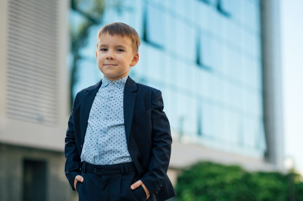 Boy in classic dark blue business costume with arms in pockets