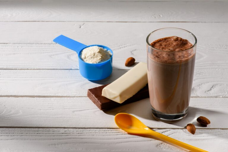 glass of protein shake with energy bars on white wooden table