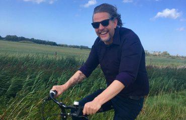 Frank op de fiets in Zeeland, blauwe lucht
