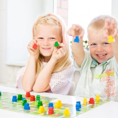 Board game and kids leisure concept - little blonde girl and boy have fun, laugh and indulge playing board game. Hold people figures in hands. yellow, blue, green wood chips