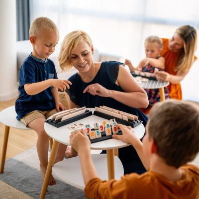 Children and woman, mother learn while playing a board game. Education, fun, children concept