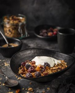 Ambachtelijke granola (hazelnoot, rozijnen, pompoen, gedroogde cranberry, sesam en zonnebloem zaadjes) met yoghurt in een zwarte kom