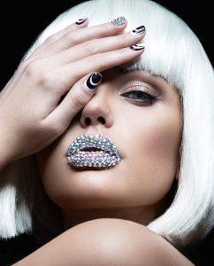 Elegant knap meisje met blonde pruik en diamanten lippen op plexiglas