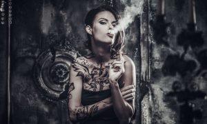 vrouw met tattoos rookt een sigaar op plexiglas
