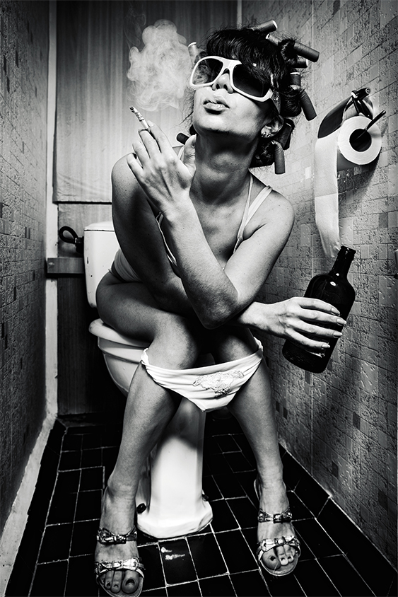 Girl sits on a toilet with cigarettes and alcohol