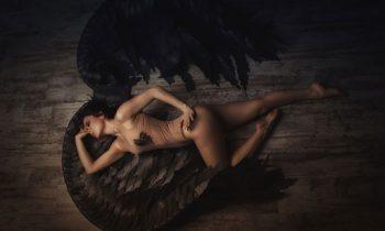 Sexy engel met zwarte vleugels op plexiglas