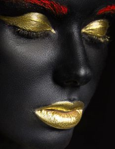 dark skinned girl with gold make up op plexiglas