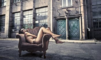 Plexiglas schilderij - Beautiful woman lying on an armchair on a city street