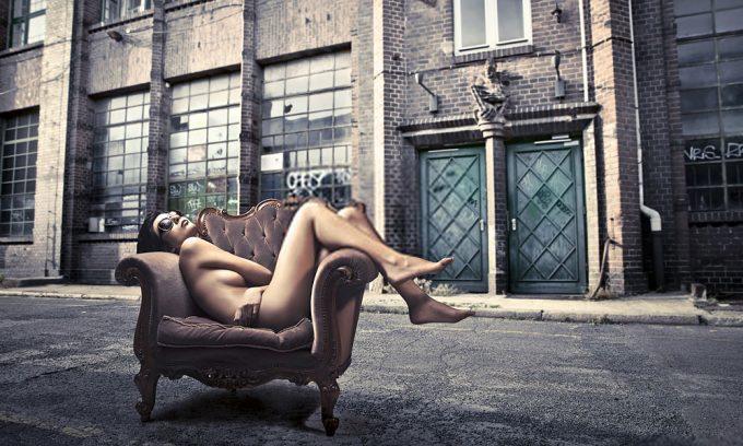 Plexiglas schilderij - Beautiful woman lying on an armchair on a city street