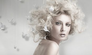 Plexiglas schilderij - Attractive blond beauty with origami on background