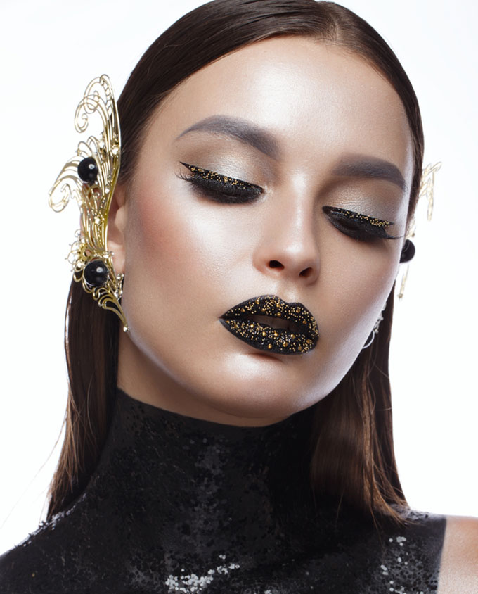 Beautiful girl with black creative art make-up and gold accessories