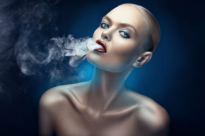 beautiful woman with red lips smokes