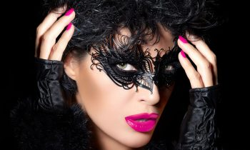 Sexy model woman in creative masquerade eye makeup with black detail