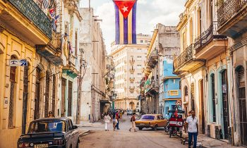 A cuban flag with holes waves over a street in Central Havana