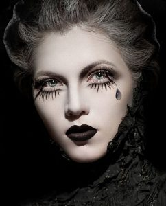 Woman in black clothes with expressive dark makeup