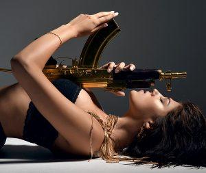 sexy brunette woman lying with fashion gold ak-47