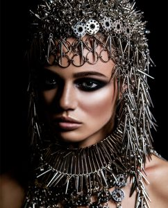 model with metallic headwear and dark makeup