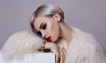 Beautiful blond young woman wearing white winter fur