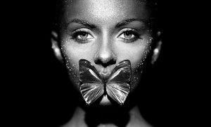 woman in bright sparkles and lights posing with butterfly
