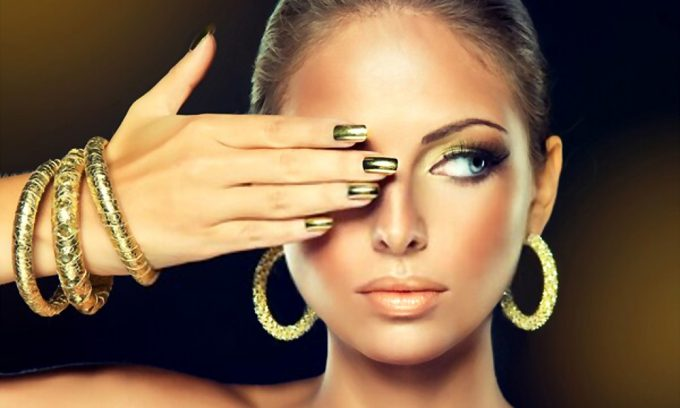 model girl with Golden makeup and gold metal manicure nails