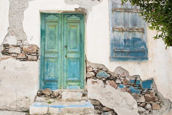 Old wooden door of a shabby house facade