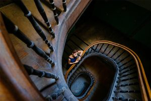woman standing on old round wooden staircase